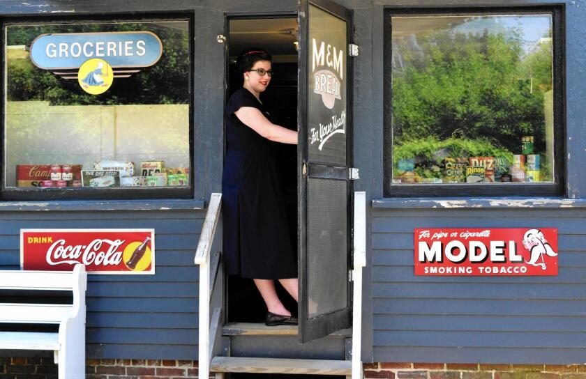 A costumed role-player stands ready to talk to visitors about the 1940s-themed general store at Strawbery Banke Museum.