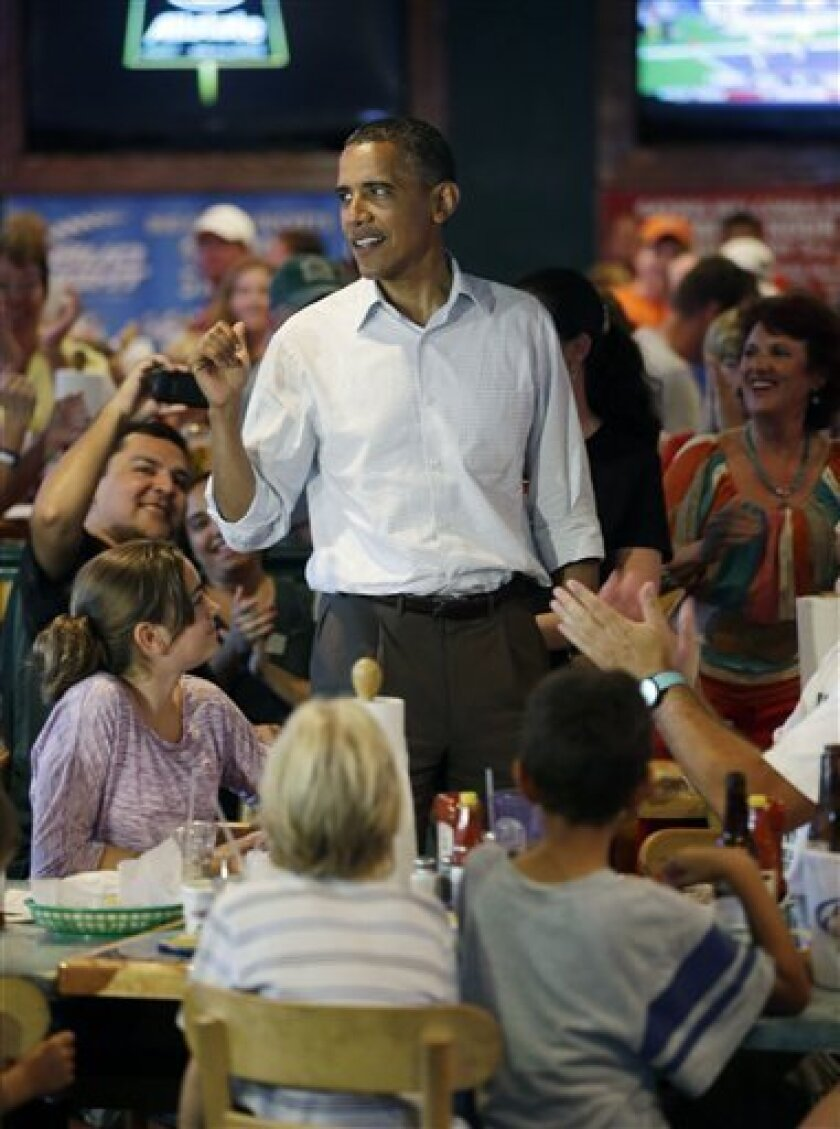 President Barack Obama greets patrons during an unschedule stop at Gator's Dockside, Saturday, Sept. 8, 2012, in Orlando, Fla. (AP Photo/Pablo Martinez Monsivais)