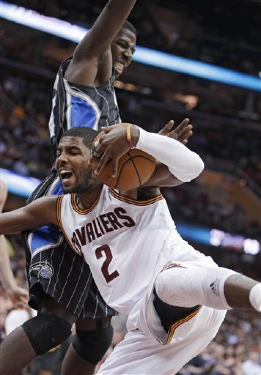 Cleveland Cavaliers' Kyrie Irving (2) grabs a rebound against Orlando Magic's Andrew Nicholson during the second quarter of an NBA basketball game Friday, Feb. 8, 2013, in Cleveland. (AP Photo/Mark Duncan)