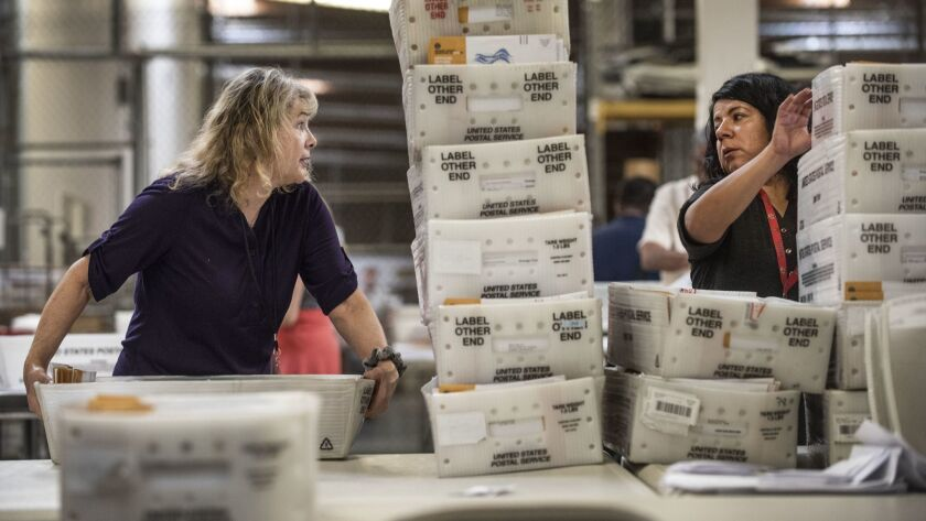 Orange County Registrar of Voters employees Barbara Strauss, left and Hilda Rodriguez, right, grab t