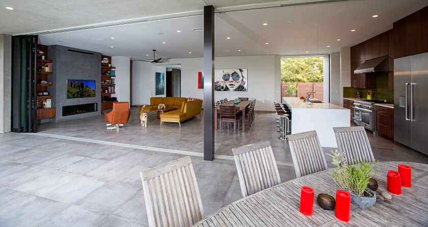 The kitchen, living and dining areas open completely to the covered deck overlooking Juniper Canyon in South Park.