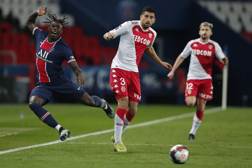 PSG's Moise Kean, left, challenges for the ball with Monaco's Guillermo Maripan during the French League One soccer match between Paris Saint Germain and Monaco, at the Parc des Princes stadium, in Paris, France, Sunday, Feb. 21, 2021. (AP Photo/Francois Mori)
