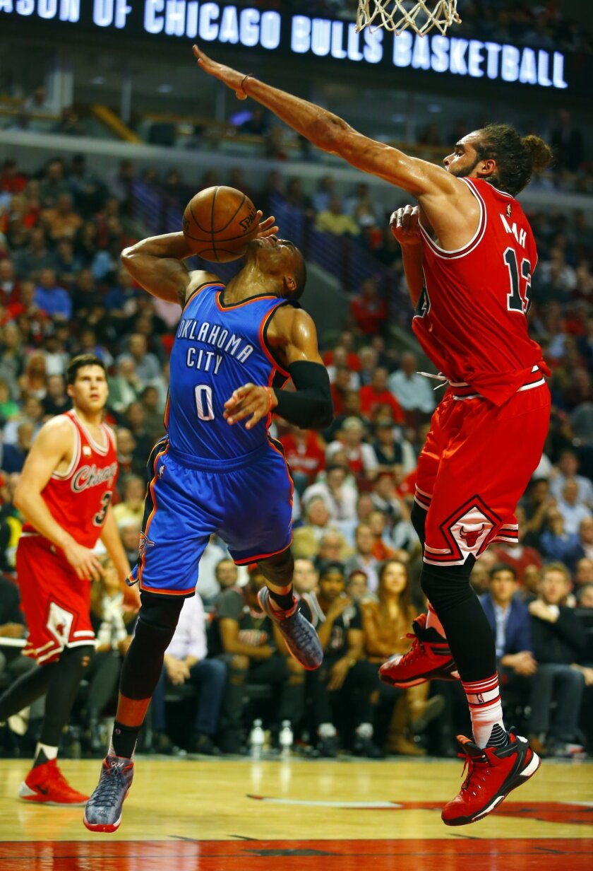 Chicago Bulls center Joakim Noah (13) blocks the shot of Oklahoma City Thunder guard Russell Westbrook (0) during the second half of an NBA basketball game in Chicago, on Thursday, Nov. 5, 2015. The Bulls won the game 104-98. (AP Photo/Jeff Haynes)
