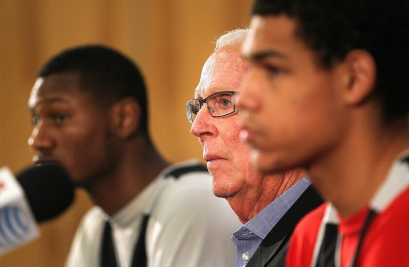 San Diego State University basketball coach Steve Fisher, at times flanked by players Skylar Spencer, left, and Trey Kell, addressed questions during a press conference at the school Tuesday. The NCAA dropped allegations of wrongdoing by the team earlier in the day.