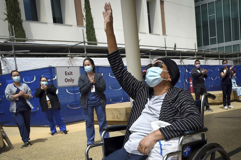 """FILE - In this May 19, 2020, file photo, Karen Parker-Bryant, 64, raises a hand skyward after she was released from Clovis Community Hospital after a battle with COVID-19, in Fresno, Calif. Hospitals in the heart of California's Central Valley are running out of beds in their intensive care units because of an influx of coronavirus patients, prompting officials on Friday, Sept. 3, 2021, to declare an official """"surge."""" (John Walker/The Fresno Bee via AP, File)"""
