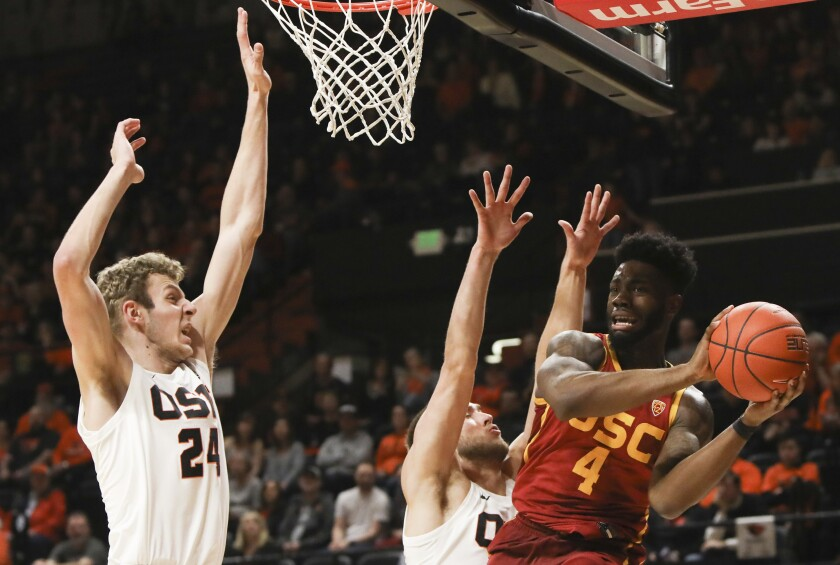 USC's Daniel Utomi (4) passes away from the basket to avoid Oregon State's Kylor Kelley (24) and Tres Tinkle (3) during the first half on Saturday.