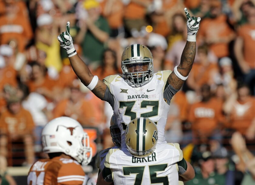 Baylor's Shock Linwood (32) is lifted by teammate Troy Baker after he scored a touchdown against Texas during the second half of an NCAA college football game, Saturday, Oct. 4, 2014, in Austin, Texas. (AP Photo/Eric Gay)