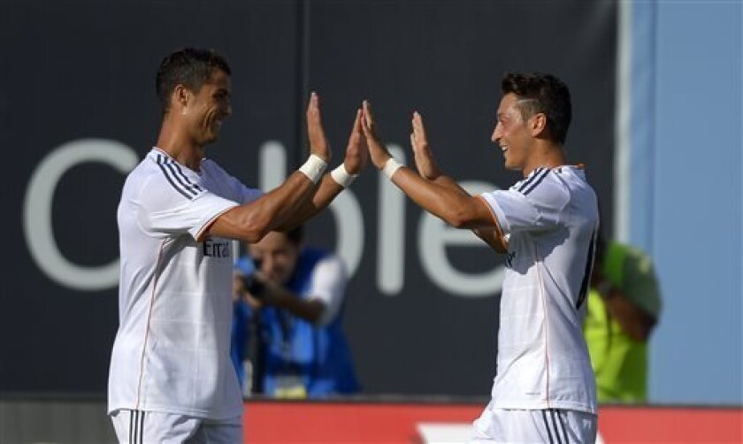 Real Madrid midfielder Mesut Ozil, right, is congratulated by teammate Cristiano Ronaldo after scoring during the first half of their International Champions Cup soccer match against Everton, Saturday, Aug. 3, 2013, in Los Angeles. (AP Photo/Mark J. Terrill)
