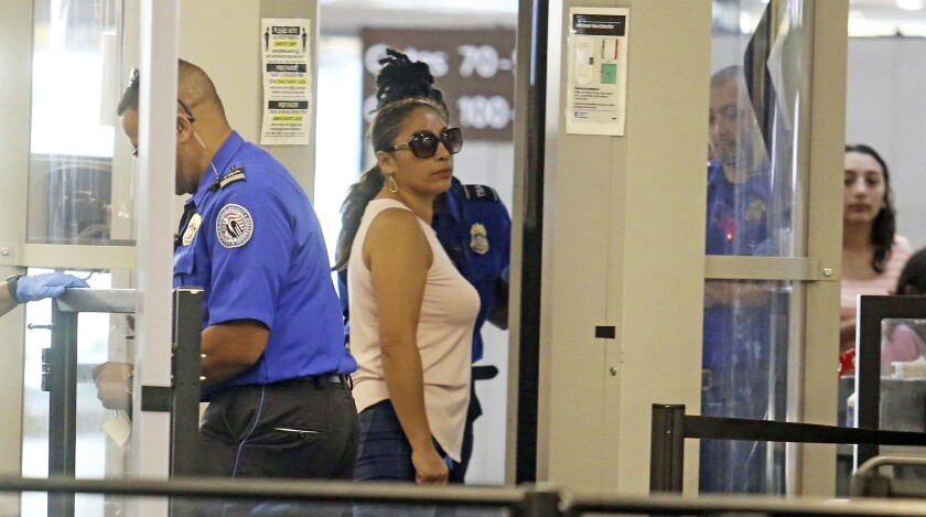 Alejandra Juarez passes through preflight screening before leaving for Mexico at Orlando International Airport on Friday.