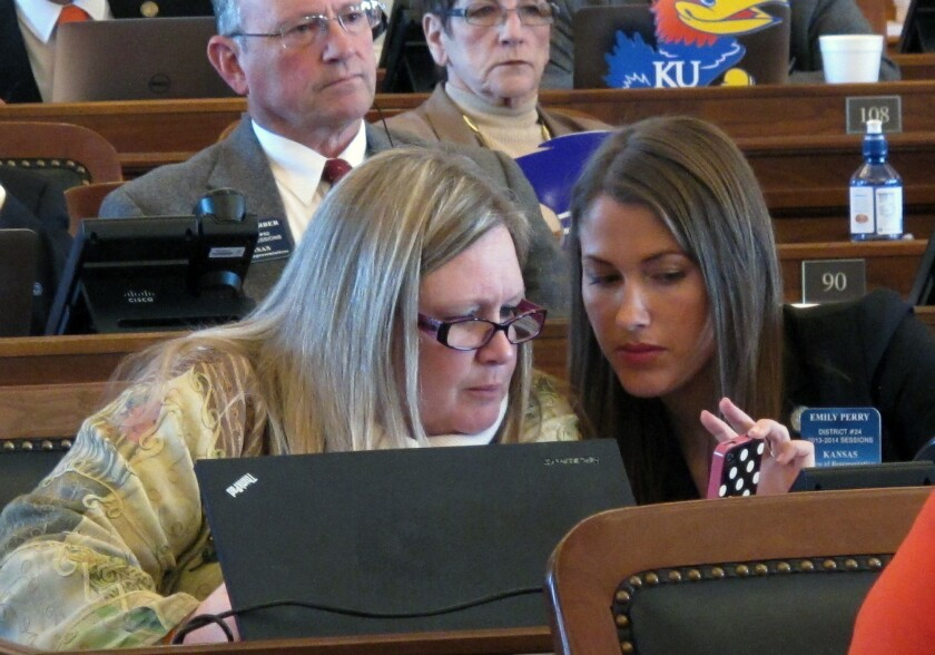 Kansas state Reps. Julie Menghini, left, and Emily Perry confer during a House debate on a bill dealing with gay marriage.