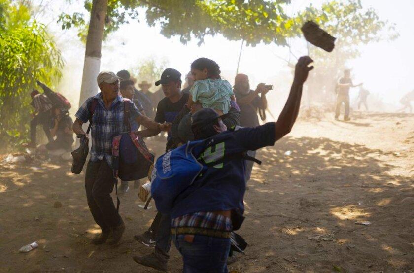 Un migrante centroamericano arroja una roca a un elemento de la Guardia Nacional mexicana después de haber cruzado el río Suchiate de Guatemala a México, cerca de Ciudad Hidalgo, México.