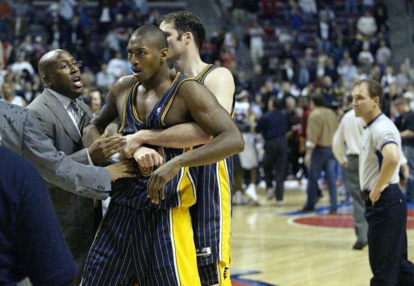 FILE - In this Nov. 19, 2004 file photo, Indiana Pacers' Ron Artest is restrained before being escorted off the court following a fight with the Detroit Pistons and fans in Auburn Hills, Mich. Artest, now known as Metta World Peace and with the New York Knicks, believes Marcus Smart can learn from