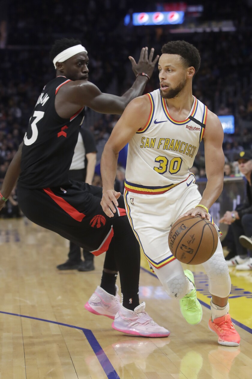 Warriors guard Stephen Curry slips past Raptors forward Pascal Siakam during the second half of a game March 5 at the Chase Center.