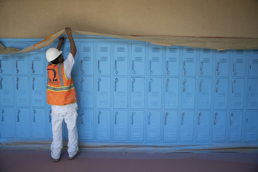 Painting contractor Jose Ortiz works on a hall of lockers at Oliver Wendell Holmes Middle School on Aug. 18 in Northridge.
