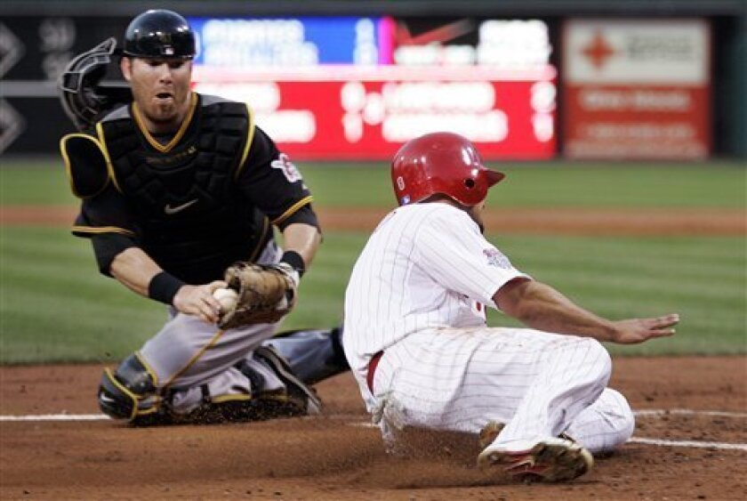 Philadelphia Phillies' Shane Victorino beat the tag of Pittsburgh Pirates catcher Ryan Doumit to score on a single by Chase Utley in the third inning of a baseball game Friday, July 10, 2009, in Philadelphia. (AP Photo/Tom Mihalek)