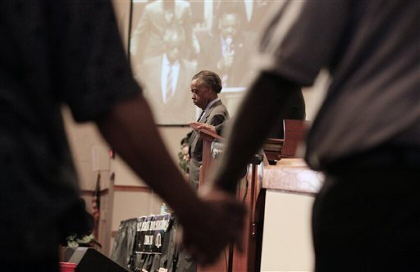 Rev. Al Sharpton, center, listens as The Rev. Jesse Jackson, not seen, leads a prayer during a community forum at the Macedonia Baptist Church in Eatonville, Fla., Monday, March 26, 2012. Students also held rallies on the campus of Florida A&M University in Tallahassee and outside the Seminole Coun