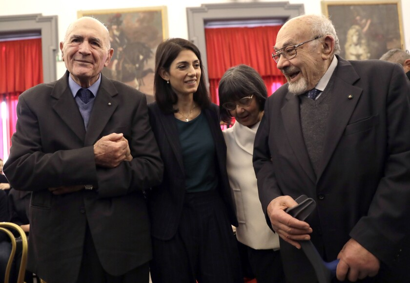 FILE - In this Friday, Jan. 27, 2017 filer, Rome's mayor Virginia Raggi, second from left, poses for a photo with Holocaust survivors Sami Modiano, left, and Piero Terracina, right, during an event to commemorate the International Holocaust Remembrance Day in the Rome's Capitol Hill. Piero Terracina, 91, one of the last survivors of Italy's tiny Jewish community who were deported to Nazi death camps during World War II, has died. Rome's Jewish Community said Terracina died on Sunday, Dec. 8, 2019. He was deported to the complex of Auschwitz-Birkenau camps with his family, where his parents, three siblings and other relatives perished. (AP Photo/Alessandra Tarantino, File)