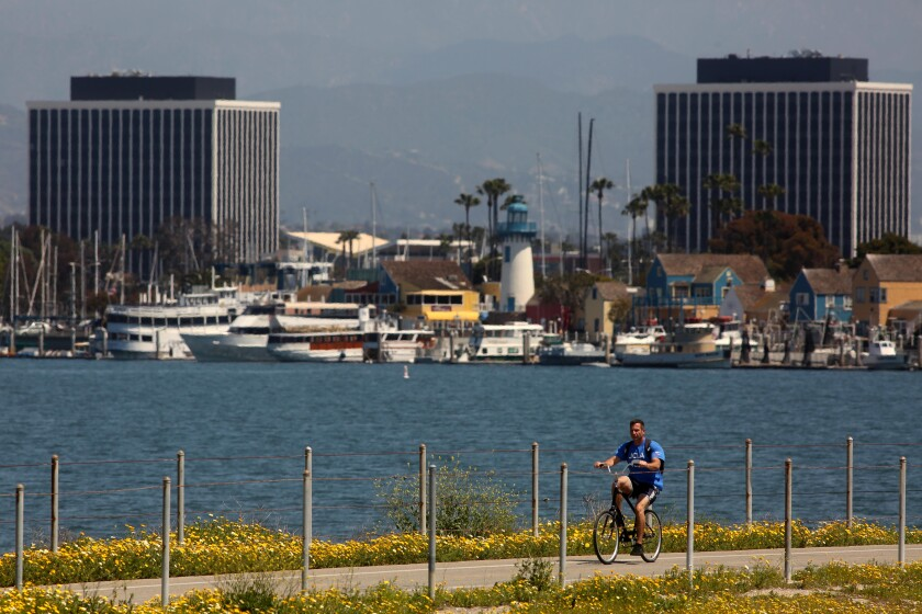 A bicyclist rides on the Ballona Creek bike path against a backdrop of Marina Del Rey.