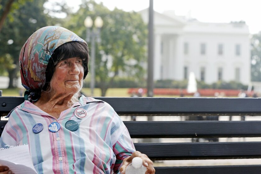 FILE - In this Sept. 12, 2013 file photo, Concepcion Picciotto, who holds a constant peace vigil in Lafayette Park across from the White House in Washington, sits on a park bench in the park. Picciotto, the protester who maintained a peace vigil outside the White House for more than three decades, a demonstration widely considered to be the longest-running act of political protest in U.S. history, has died. The Washington Post reports Picciotto died Monday, Jan. 25, 2016, at a housing facility for homeless women. She was believed to be 80. (AP Photo/Charles Dharapak, File)