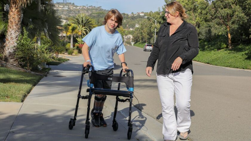 Ian McFarland uses his walker on the street near his home. With him is his aunt Melissa Coleman.