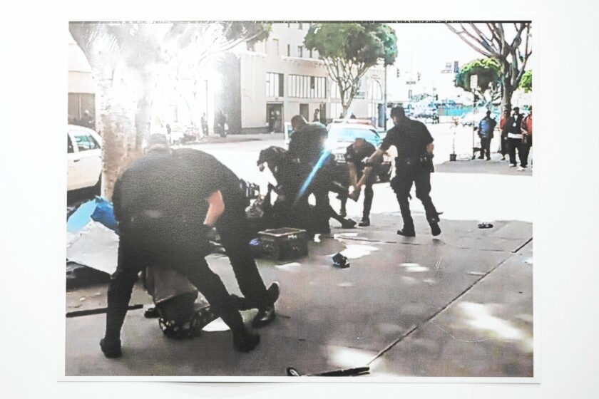 An image from cellphone video shows altercation between police and the homeless man who was killed, background.