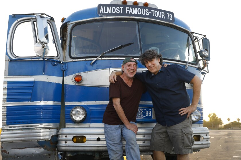 """History repeats for famed photographer Neal Preston (left) and writer and director Cameron Crowe, who worked together on Crowe's 2000 film """"Almost Famous"""" and have now reunited for Crowe's new Old Globe musical adaptation of """"Almost Famous."""" They are shown here in the parking lot of the former San Diego Sports Arena (now Pechanga Arena San Diego) on Aug. 27, 2019."""