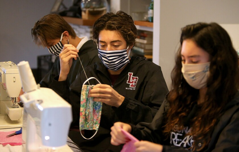 """Laguna Beach High student-athletes Myha Pinto, Michael Pinto, and Jackson Golden, from right, sew and assemble homemade cotton masks for their """"Sewing for SoCal"""" organization."""