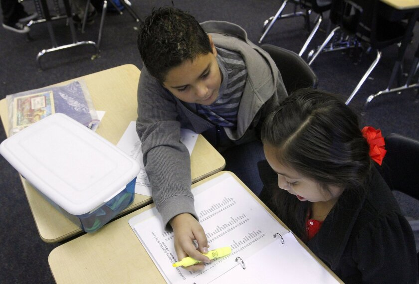 Alan Ruiz helps first-grader Elizabeth Torres with spelling at Wildomar Elementary School before the start of school on a recent Wednesday. Teacher Tim Bedley's fifth-grade GATE students are tutoring their younger schoolmates in a program that school leaders say is having profound effects on both sets of kids.