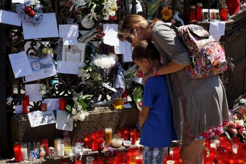 At the gate of the cathedral in Santiago de Compostela, Spain, people look at messages, flowers and candles left in memory of the victims of a train derailment.