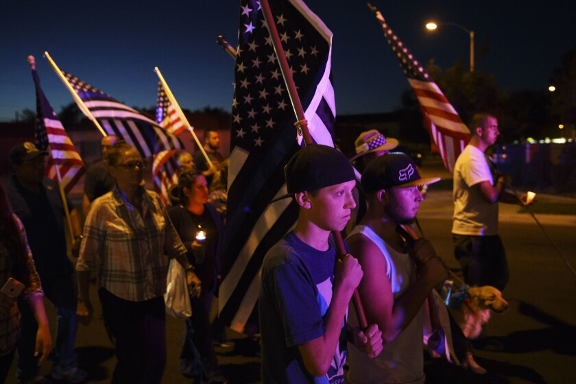 People mourn the death of Los Angeles County Sheriff's deputy Sgt. Steve Owen during a candlelight vigil in Lancaster on Saturday.