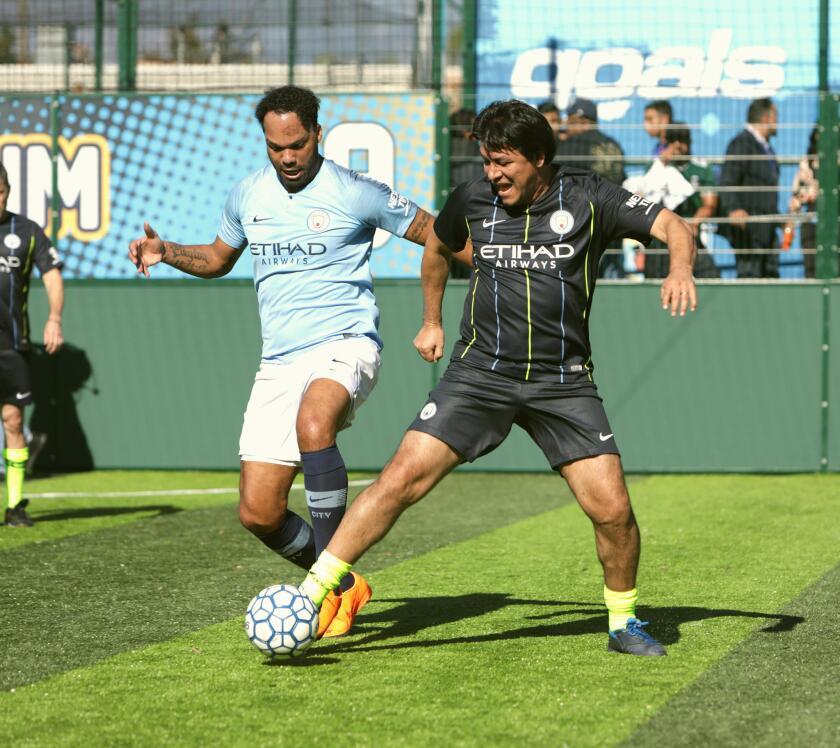 El exjugador del Man City Joleon Lescott (i) disputa el balón con la exestrella del Tri Claudio Suarez (d) durante una cascarita en Goals Covina.