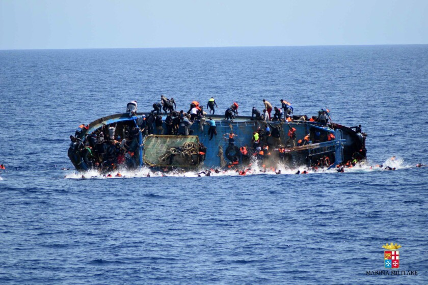 Migrants jump out of a boat as it overturns off the Libyan coast May 25.