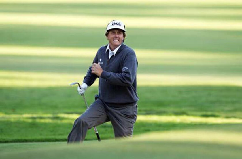 Phil Mickelson runs from the front bunker to see where his shot landed on the 10th hole on Friday.