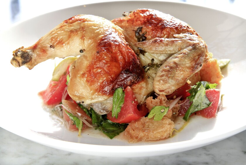 According to Google, chicken recipes were the most-searched-for recipes of 2014. Pictured is a wood roasted half chicken with heirloom tomato bread salad served at Tar & Roses restaurant.