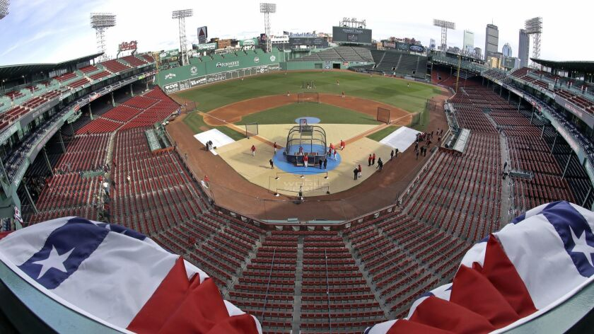 Bunting billows up in the wind at Fenway Park's upper deck as Boston Red Sox players work out, Sunda