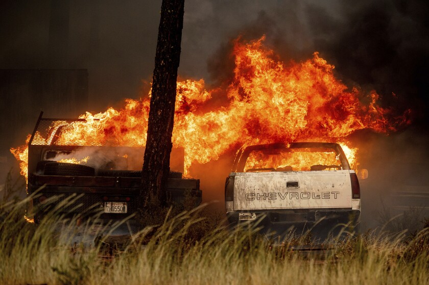 Las llamas consumen vehículos en un desguace mientras el incendio Dixie arde en Chester, California
