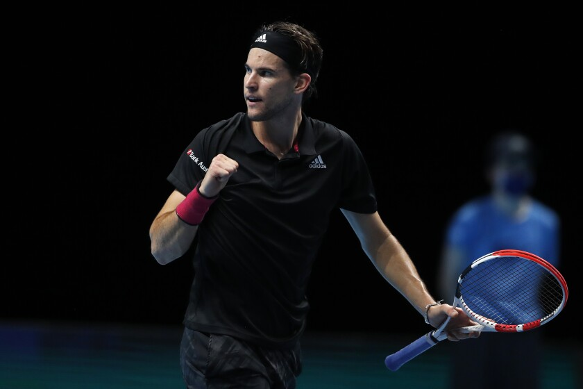 Dominic Thiem celebrates while holding his tennis racket after winning the first set against Novak Djokovic.