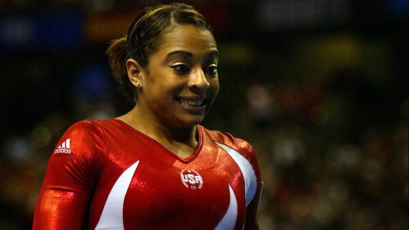 Tasha Schwikert reacts after competing in the uneven bars at the 2003 world gymnastics championships.