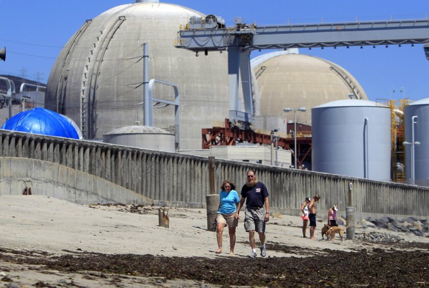 Beachgoers walk on the sand near the San Onofre nuclear power plant in San Clemente. The plant was shut down in 2012. Closed nuclear reactors are dipping into funds set aside for their eventual dismantling to build waste storage on-site, raising questions about whether there will be enough money when the time comes.