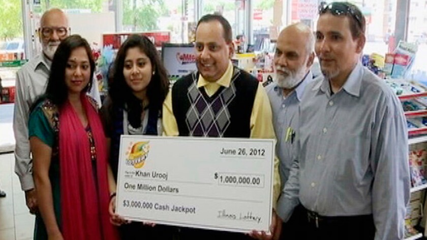 Urooj Khan holds a ceremonial check in Chicago for the $1 million he won in the Illinois lottery.