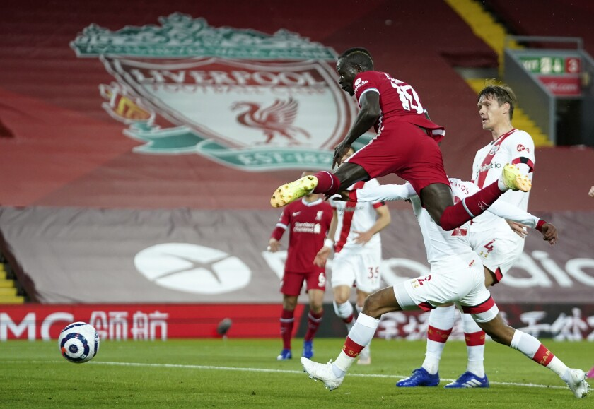 Liverpool's Sadio Mane, front, scores his side's opening goal during the English Premier League soccer match between Liverpool and Southampton at Anfield stadium in Liverpool, England, Saturday, May 8, 2021. (Zac Goodwin/Pool via AP)