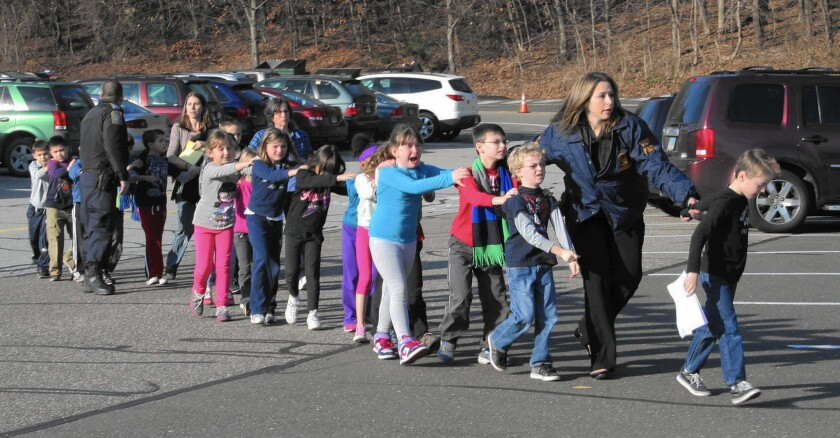 Children are led by police from Sandy Hook Elementary School in Newtown, Conn., after the shooting on Dec. 14, 2012, in which 20 first-graders and six educators were killed.