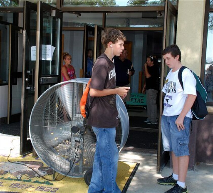 Chandler Lacher, left, and Cody Clarambeau, both 8th graders, stand near a fan blowing air into a school building in Fort Pierre, S.D., on Wednesday, Aug. 29, 2012, after the Stanley County School District closed early because of extreme heat. More than two dozen South Dakota schools let students go home early Wednesday because temperatures topping 100 degrees made classrooms that are not air conditioned unbearable. (AP Photo/Chet Brokaw)