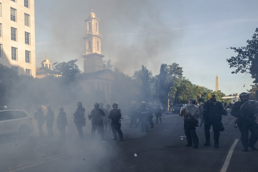 Police use tear gas to force protesters away from St. John's Church near the White House on June 1 for a Trump photo op.