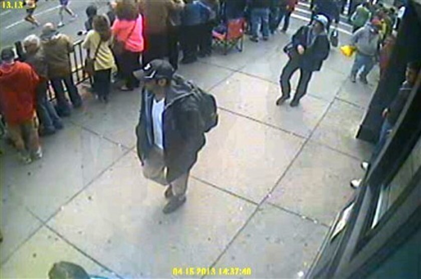 This frame grab from a video released by the FBI on Thursday, April 18, 2013, shows what the FBI are calling suspect number 1, front, in black cap, and suspect number 2, in white cap, back right, walking near each other through the crowd in Boston on Monday, April 15, 2013, before the explosions at the Boston Marathon. (AP Photo/FBI) (AP Photo/FBI)