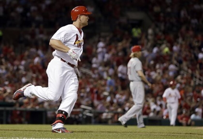 St. Louis Cardinals' Matt Holliday, left, rounds the bases after hitting a two-run home run off Cincinnati Reds starting pitcher Bronson Arroyo during the sixth inning of a baseball game Tuesday, April 30, 2013, in St. Louis. (AP Photo/Jeff Roberson)