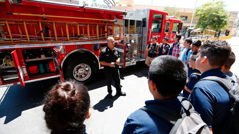 Los Angeles Fire Capt. Eddie Marez explains the workings of a fire engine to students at the new Wilson High School Firefighter Academy Magnet.
