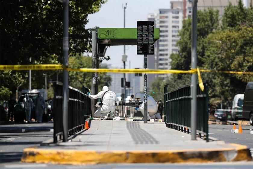 Chilean police search for evidence after five people were wounded in an explosion at a bus stop in Santiago on Friday, Jan. 4. EFE-EPA/Alberto Valdes
