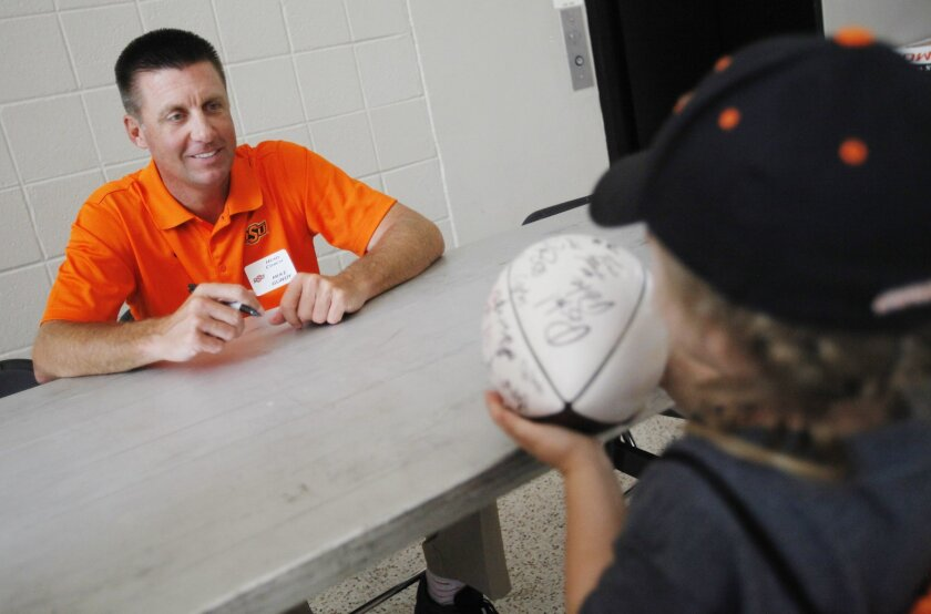 Four year old Khali Winters of Chickasha has her football signed by Oklahoma State football coach Mike Gundy during Oklahoma State's fan appreciation day in Stillwater, Okla., Saturday, Aug. 2, 2014. (AP Photo/The Oklahoman, KT King) LOCAL STATIONS OUT (KFOR, KOCO, KWTV, KOKH, KAUT OUT); LOCAL WEBSITES OUT; LOCAL PRINT OUT (EDMOND SUN OUT, OKLAHOMA GAZETTE OUT) TABLOIDS OUT