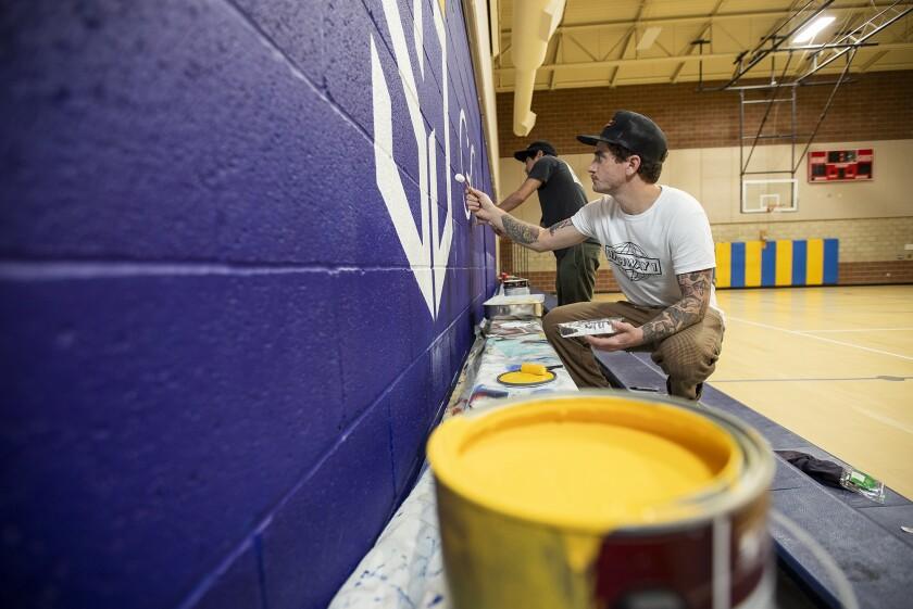 Cody Parole, a Costa Mesa-based artist, and Joe Suzuki work on a mural at St. Joachim Catholic School in Costa Mesa this month.